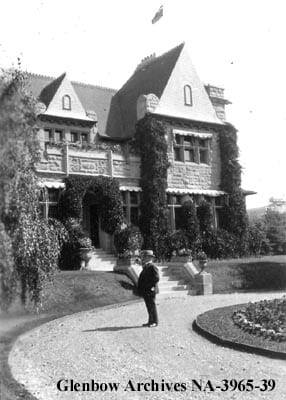 patrick burns standing outside his sandstone mansion in Calgary